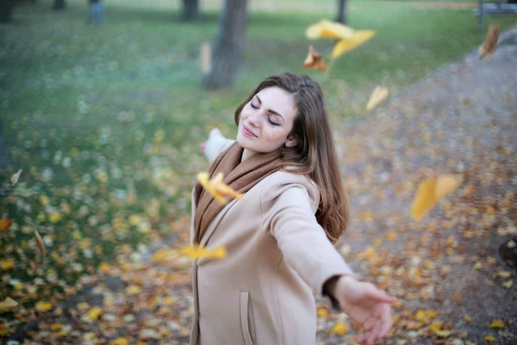 Woman with eyes closed spinning around as leaves fall