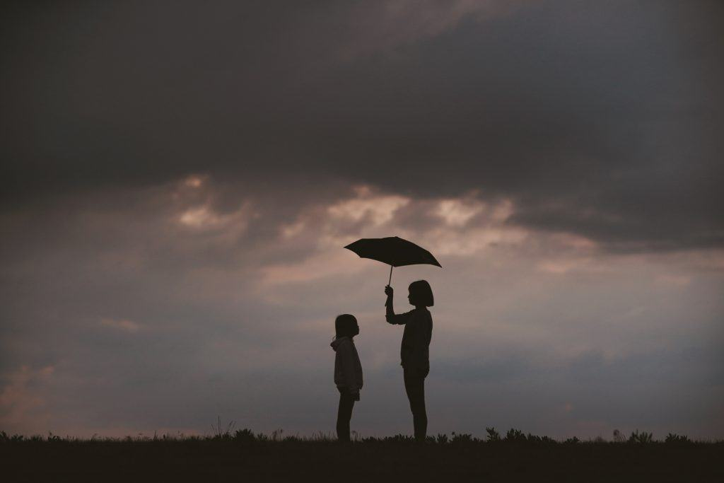 Two people standing with one holding umbrella
