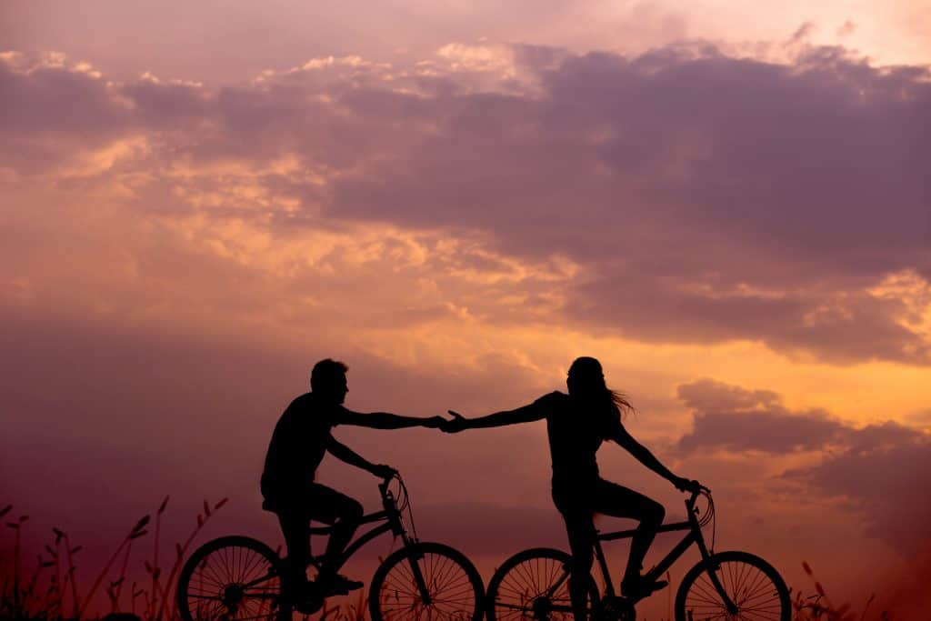 Two people riding bikes and holding hands