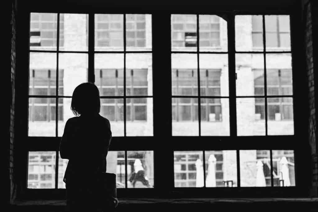 black and white photo of woman staring out of window