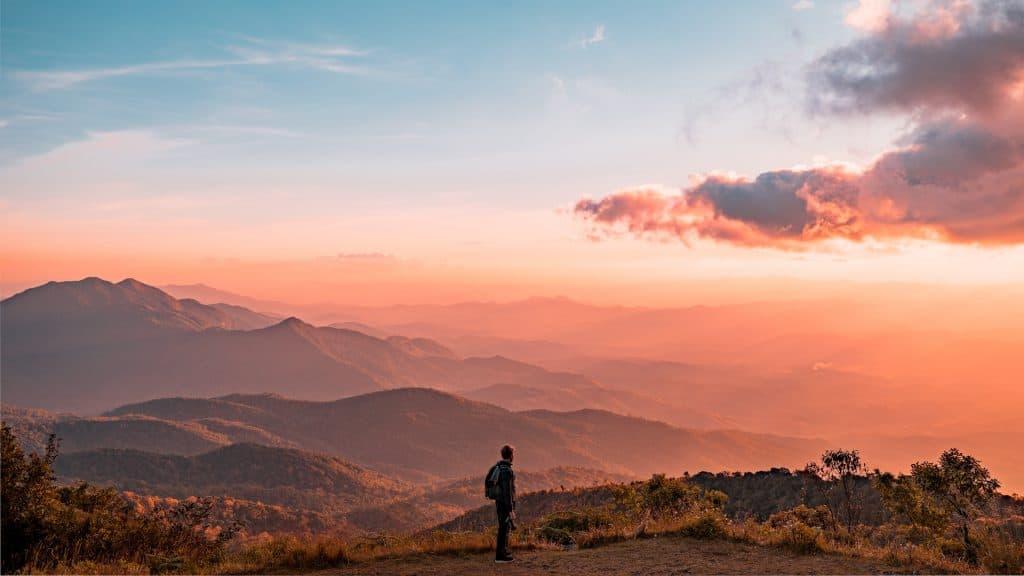 Man stood overlooking sunset across mountain range