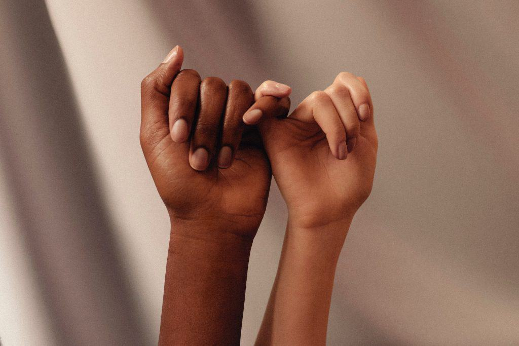 Two people linking their pinky fingers