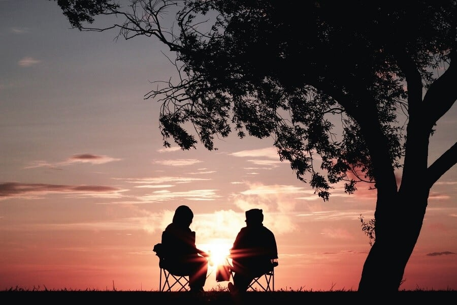 Couple sat on camping chairs in the sunset