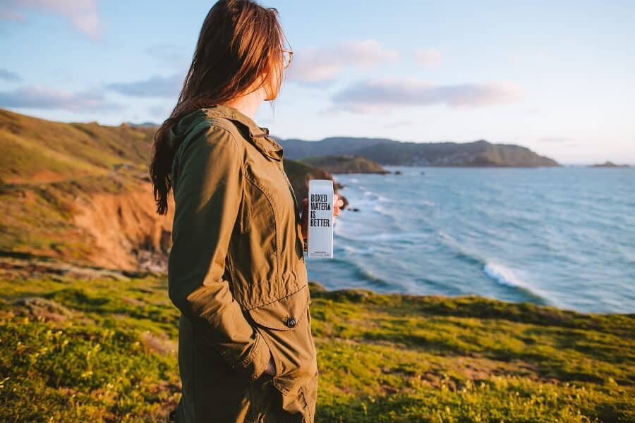 Woman with drink standing looking off a cliff